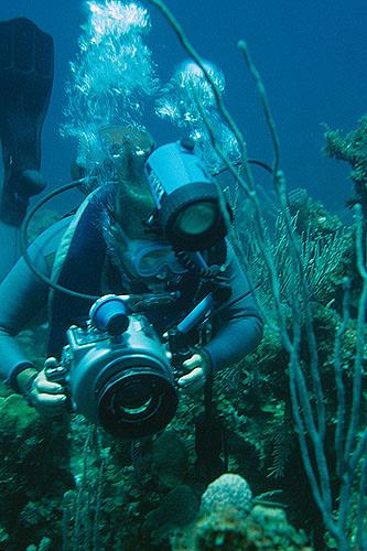 Fotograf in voller Montur unter Wasser
