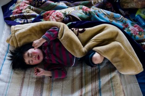 Ein Junge aus Fukushima erwacht in einer Notunterkunft. Über 80.000 Menschen verloren durch den Reaktorunfall ihr Heim