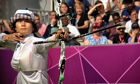 Ki Bo Bae beim Bogenschießen. Sogar der fliegende Pfeil ist zu erkennen